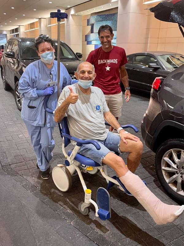 Jon Friedman being pushed in wheelchair